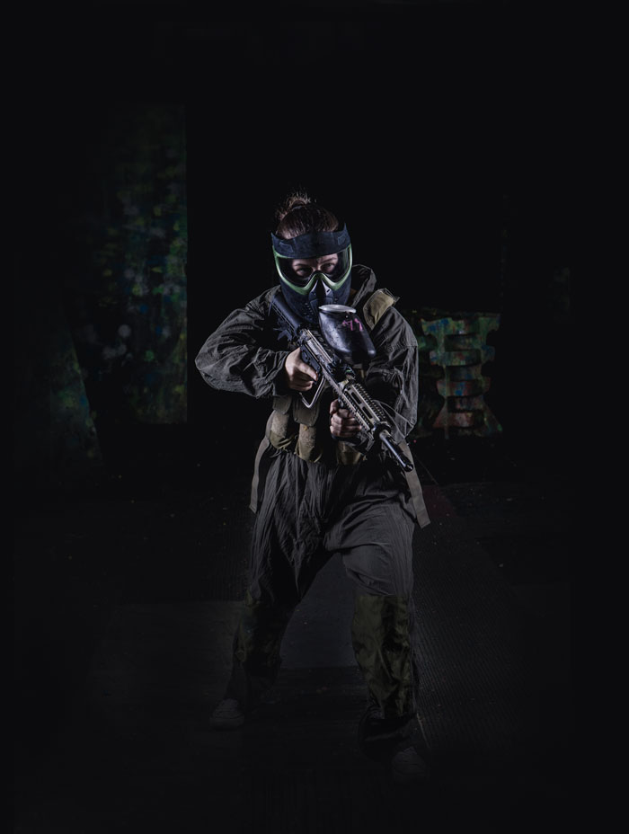 female paintball player in full flight suit and gear